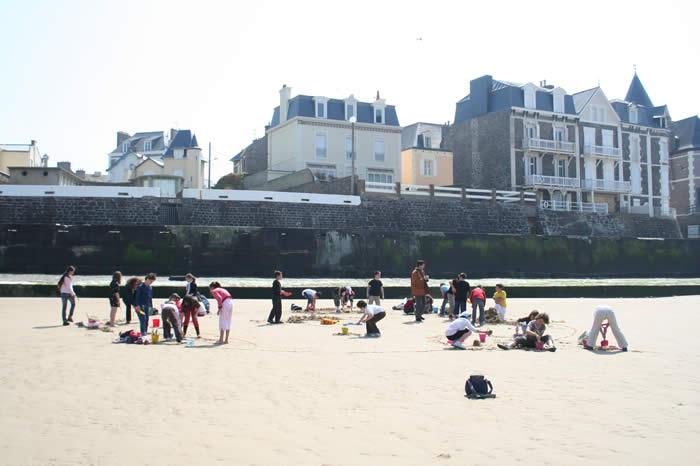 Classe de CM2 réalisant des maquettes en sable sur la plage à l'issue d'une série d'intervention sur le thème de l'histoire des fortifications.